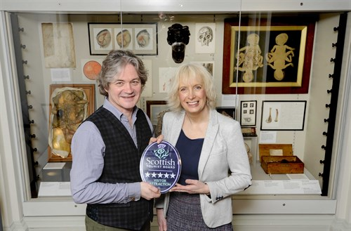 VisitScotland Regional Director, Manuela Calchini (right), presents Chris Henry (left), Director of Heritage at The Royal College of Surgeons of Edinburgh, with Surgeons'' Hall Museum's Five Star Quality Assurance award